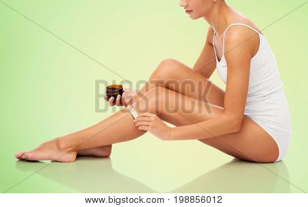 beauty, depilation, epilation, hair removal and people concept - beautiful woman with applicator applying depilatory wax to her leg over green background
