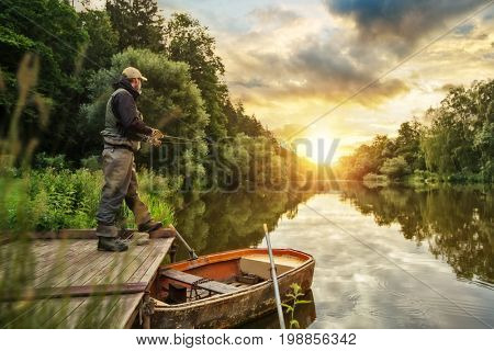 Sport fisherman hunting predator fish from wooden pier. Outdoor fishing in river during sunrise. Hunting and hobby sport.