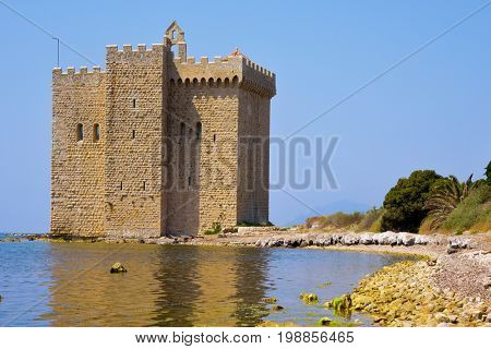 a view of the medieval fortified monastery of the Lerins Abbey in the Saint-Honorat island, France, surrounded by the Mediterranean sea
