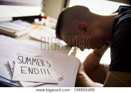 closeup of a concerned man sitting at his office desk and a note in the foreground with the text summers end handwritten in it
