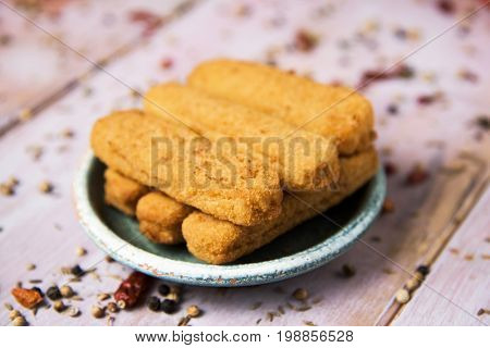 some appetizing fish sticks served in a worn out green plate, on a rustic wooden table