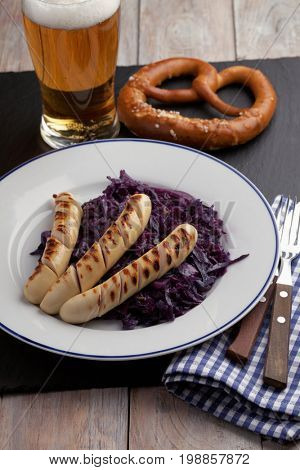 Grilled sausages with braised red cabbage, glass of beer, and pretzel