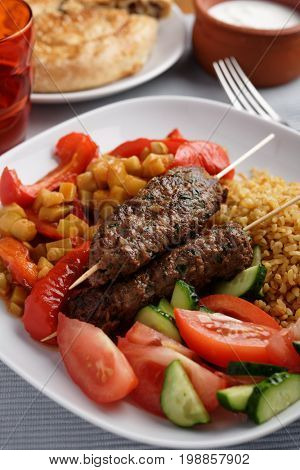 Turkish dinner with kebabs, bulgur, braised vegetables, and fresh tomato and cucumber salad