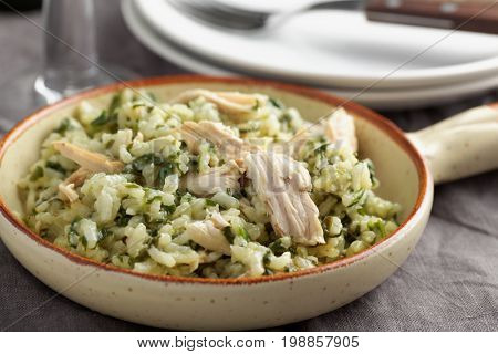 Chicken risotto with pesto sauce on a rustic table