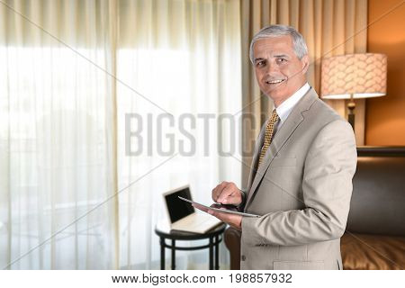Businessman in hotel room with tablet computer. Business travel concept.