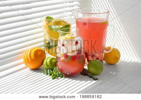 Glass jugs with different lemonades on window sill poster