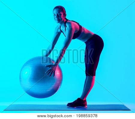 one mixed races woman exercsing fitness pilates exercices isolated on blue blackground
