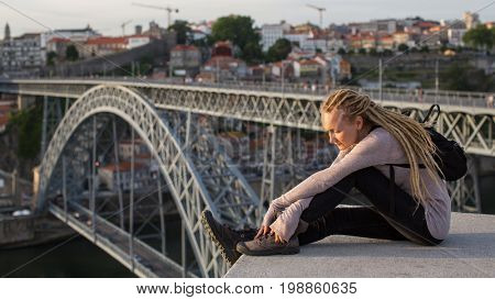 Beautiful young woman sitting on the background of the Dom Luis I bridge in Porto, Portugal.