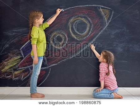 Back to school! Two happy cute industrious children are drawing rocket on blackboard. Kids are learning in class.