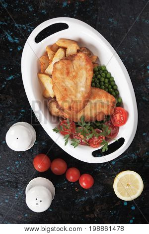 Breaded chicken steak with roasted potato and green peas