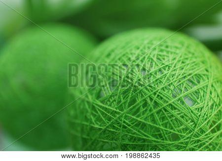 Green wicker ball on blurred background, closeup