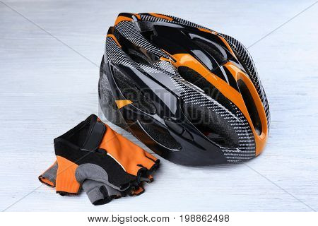 Bicycle helmet and gloves on wooden background
