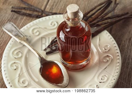 Bottle and spoon with aromatic extract and vanilla beans on plate