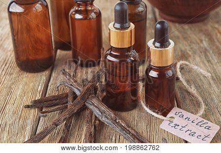 Bottles with aromatic extract and dry vanilla beans on table