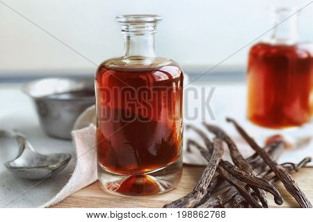 Bottle with aromatic extract and dry vanilla beans on table