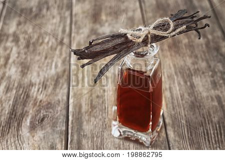 Bunch of dry vanilla beans and bottle with aromatic extract on table