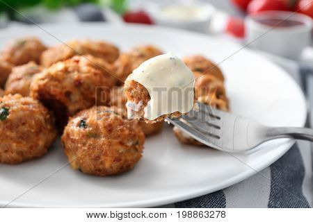 Fork and plate with delicious turkey meatballs on table, closeup