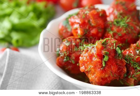 Bowl with delicious turkey meatballs and tomato sauce on table, closeup