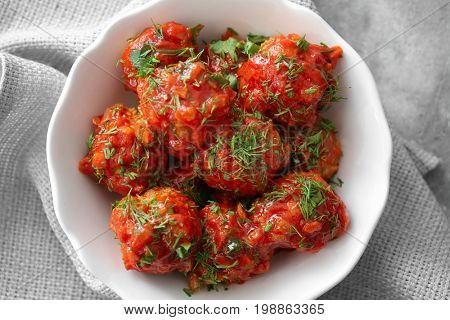 Bowl with delicious turkey meatballs and tomato sauce on table