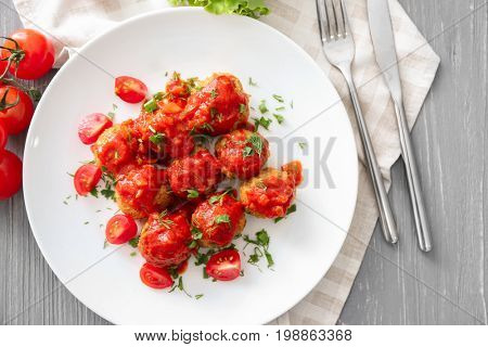 Plate with delicious turkey meatballs and tomato sauce on wooden table
