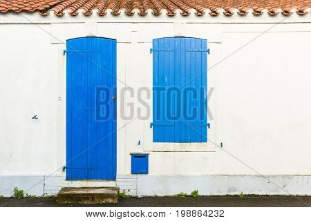 House facade with blue blinds and door in Noirmoutier island, France