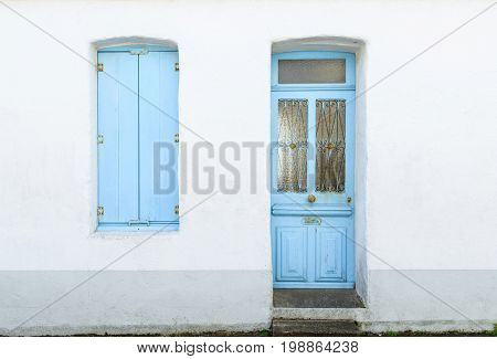 House facade with pastel blue blinds and door in Noirmoutier island, France