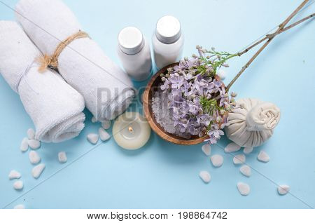 lilac flowers ,salt in bowl , candle,soap with herbal ball ,oil ,towelon blue background