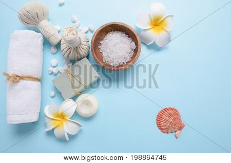 salt in bowl , frangipani ,candle,soap with herbal ball ,shell, on blue background
