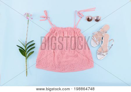 pink skirt and lilac flowers ,sunglasses, shoes on blue background .