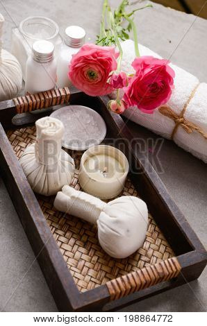 Spa setting with ranunculus and ball, salt in bowl,oil, candle in basket,soap on gray background