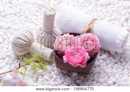 Pink ranunculus in bowl with , , herbal ball ,towelon white stones background
