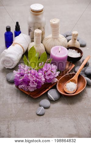 Spa setting with hygiene flowers and ball, salt in bowl, in basket on gray background