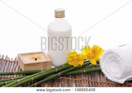 Spa setting with,roller towel ,yellow orchid, oil,bamboo grove on mat