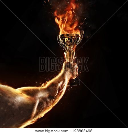 Muscular man arm holding burning trophy cup on black background. Detail of fighter hand. Concept of success, hard work and conquest of the target. High resolution