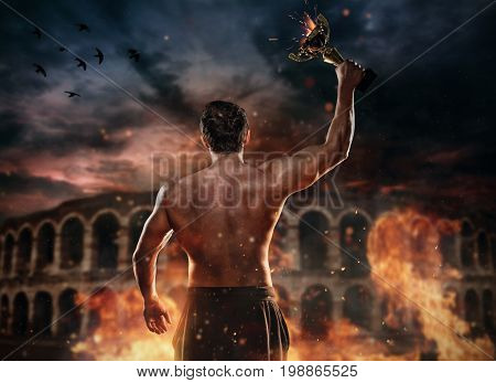 Back view of muscular man holding burning trophy cup, antique colosseum on background. Concept of success, hard work and conquest of the target. Very high resolution image