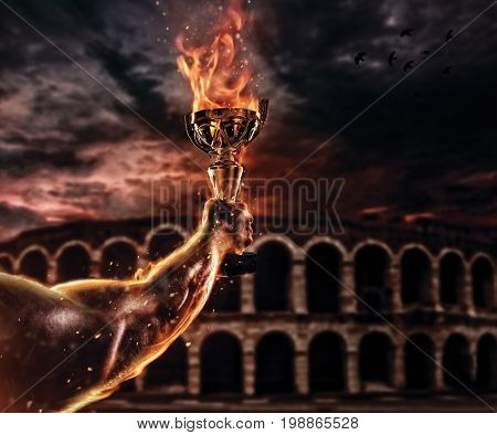 Muscular man arm holding burning trophy cup, antique colosseum on background. Detail of gladiator fighter hand. Concept of success, hard work and conquest of the target. High resolution image
