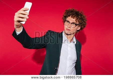 Confident stylish man in eyeglasses taking selfie while standing isolated over red background