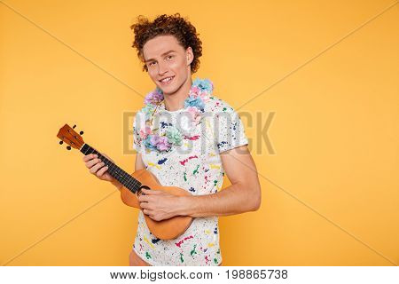Smiling attractive guy in summer clothes holding ukulele and looking at camera isolated over yellow background