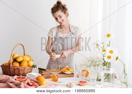 Image of lady standing indoors and squeezes out juice of a citruses. Looking aside.