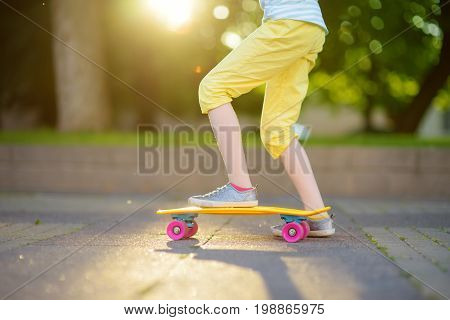 Closeup Of Skateboarder Legs. Kid Riding Skateboard Outdoor.