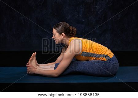 Woman doing Hatha yoga Ashtanga Vinyasa yoga asana Paschimottanasana - seated forward bend on dark grunge background