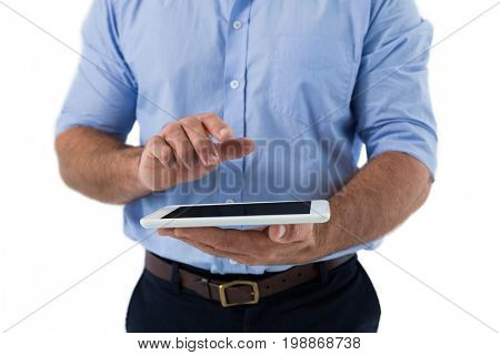 Mid section of male executive using digital tablet against white background