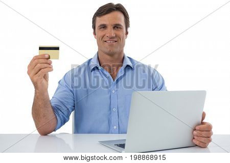 Portrait of male executive holding debit card against white background