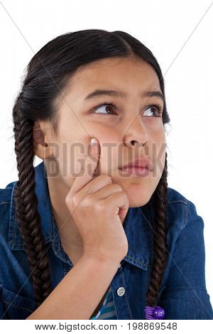 Close-up of thoughtful girl with hand on chin against white background