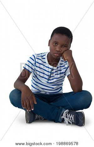 Sad boy sitting on floor against white background