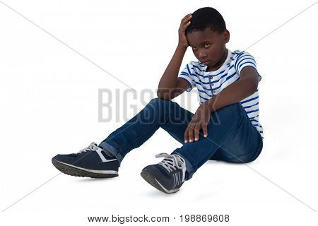 Sad boy sitting with hand on head against white background