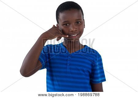 Cute boy pretending to talk on a cell phone against white background
