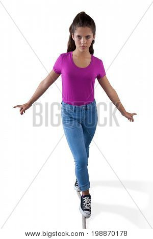 Girl walking on a tight rope and trying to keep her balance against white background