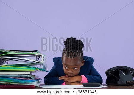 Bored businesswoman leaning by files and telephone on desk against purple wall at office