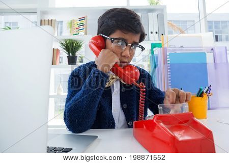 Boy pretending as businessman using land line phone at desk in office